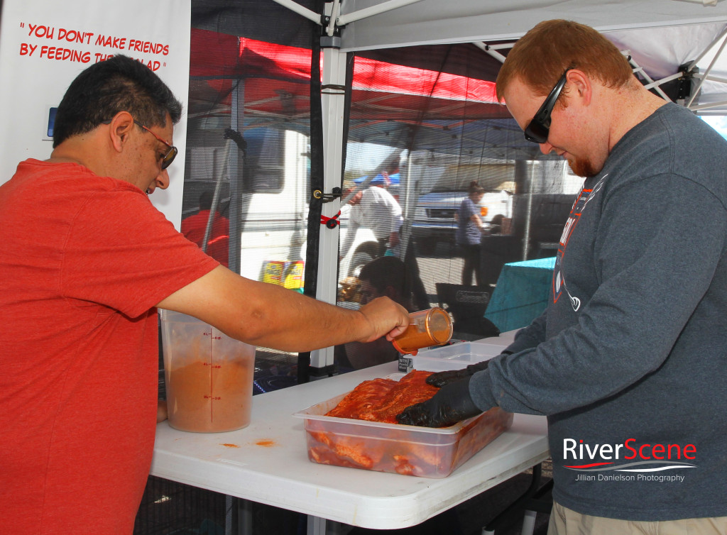 """Salvador Fuentes and Brett Witherall of team """"Grillin the Shred"""" prepare meat at the Music Brews and BBQs Friday afternoon. Jillian Danielson/RiverScene"""