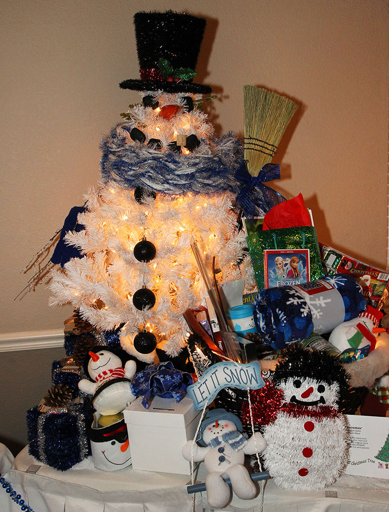 One of the trees that was raffled off during the O Christmas Tree Festival sits on the back tabled surrounded by goodies. Jillian Danielson/RiverScene