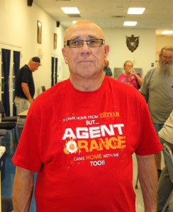 Ralph McKie poses for a photo with an Agent Orange shirt that he wore to the seminar Thursday afternoon. Jillian Danielson/RiverScene