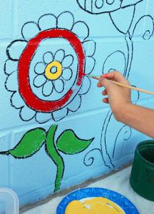 Emilee Gregg paints a flower on the wall of HAVEN Saturday morning. Jillian Danielson/RiverScene