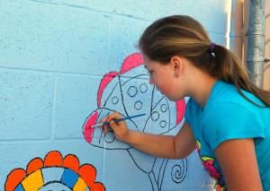 Madison Walkinshaw paints a wall on the HAVEN patio Saturday morning. Jillian Danielson/RiverScene