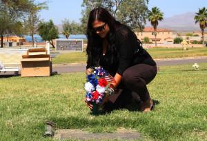 Rebecca White places flowers on a gravesite of a Veteran Tuesday morning. Jillian Danielson/RiverScene