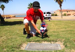 Steven Coalmer places flowers on a Veteran's gravesite on Tuesday morning.Jillian Danielson/RiverScene