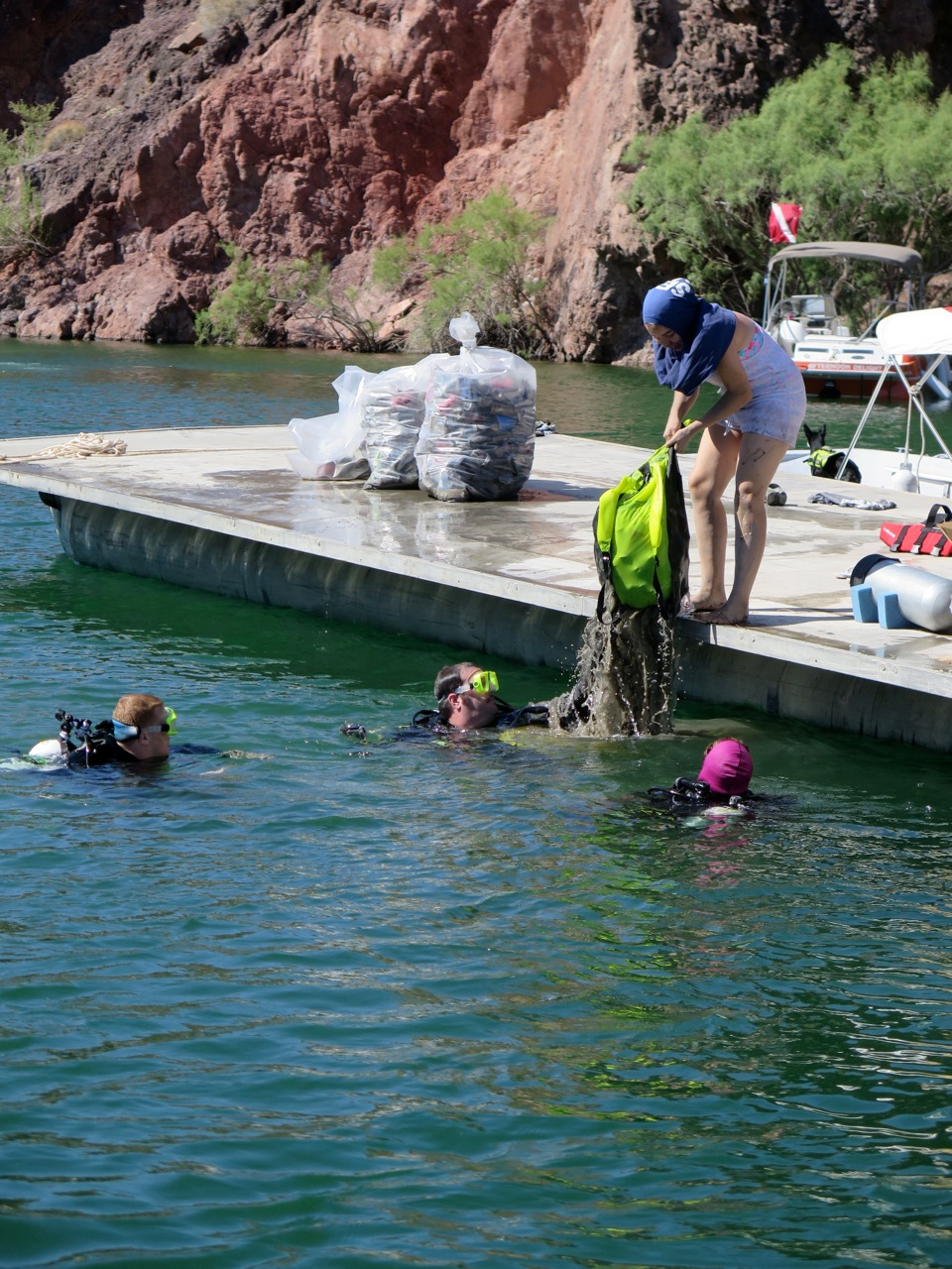 Sea Scout Joey Kasper taking trash bag from Nathan Adler, with divers John and Michele Butler.