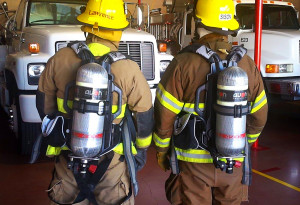 Firefighters Guy Lawrence and Jared Sison wear compressed breathing air tanks purchased by the AFG grant at the Desert Hills Fire Department Thursday afternoon. Submitted photo Stephen Bunn