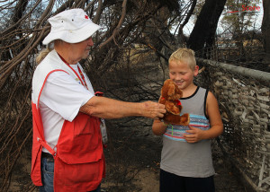 Jack Ray of the American Red Cross hands a teddy bear to Tanner Sipes-Wood while Tanner was visiting a neighbor that lost their home in the Willow Fire. Jillian Danielson/RiverScene