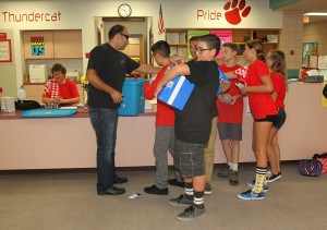 Chad Nelson hands supplies to students at Thunderbolt Middle School Friday morning. Jillian Danielson/RiverScene