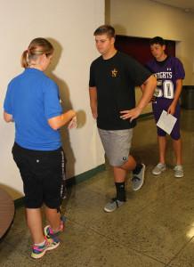 Lindsay Zanlaningham,athletic trainer, examines Travis Skelton for possible head injuries at the start of the football season. Jillan Danielson/RiverScene