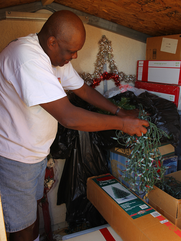 Tee Taylor pulls lights out of boxes in his storage for Christmas display. Jillian Danielson/RiverScene