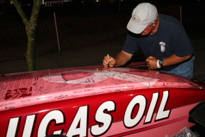 Tom Rouse signs one of the drag boats in honor of his wife, Judy, who is a ten year cancer survivor. Jillian Danielson/RiverScene