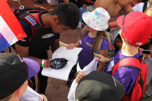 Ball Tadsapong of Thailand, autographs notebooks for Starline students at IJSBA Thursday morning. Jillian Danielson/RiverScene