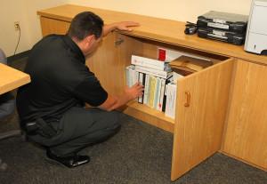 LHCPD Public Information Officer Kirk Cesena looks through handbooks that outline emergency protocol. Jillian Danielson/RiverScene