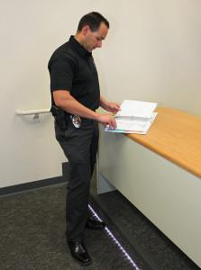 LHCPD Public Information Officer Kirk Cesena looks through a handbook which outlines emergency protocol. Jillian Danielson/RiverScene