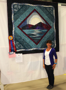 Sarah McNary stands next to her quilt Friday afternoon that won Hall Of Fame Award. Jillian Danielson/RiverScene
