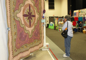 Emily Colby looks over a quilt at the Quilt Show Friday afternoon. Jillian Danielson/RiverScene
