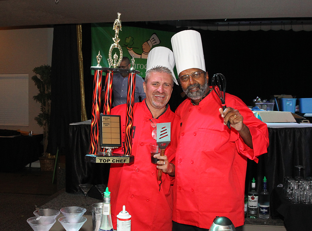 Jim Carlo and Dr. Chauhan play around with the trophy and dress up in the Top Chef uniforms. Jillian Danielson/RiverScene