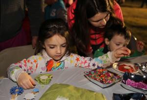 Angelina Kahn makes a craft with beads Thursday evening. Jillian Danielson/RiverScene