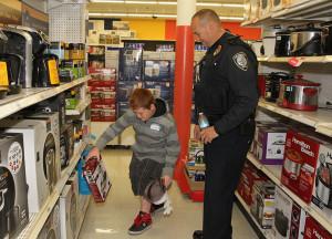 Seth Cormier shops with Officer Larry Allen Saturday morning. Jillian Danielson/RiverScene