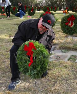 Doug Bryson lays a wreath on a gravesite of a Veteran Monday morning. Jillian Danielson/RiverScene