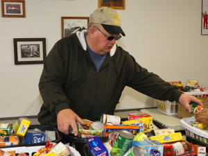 Duwayne Haynes sorts food baskets that were delivered to families Sunday morning. Jillian Danielson/RiverScene