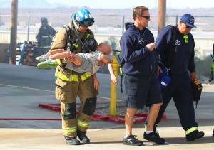 Firefighter recruit John Clark carries a mannequin victim to safety during training. Jillian Danielson/RiverScene