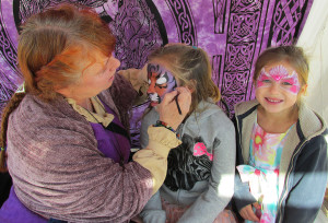 From left, Dancing Dolphins Art owner and artist Cindy Farslow paints a tiger face on 8-year-old Annabelle Zaragoza while younger sister 6-year-old Elliana poses with her own face painting Friday during the inaugural London Bridge Renaissance Faire. Jayne Hanson/RiverScene