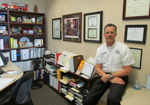 Lake Havasu City Fire Chief Dennis Mueller poses for a photo in his work space including his framed diplomas, credentials and other personal effects. Jayne Hanson/RiverScene