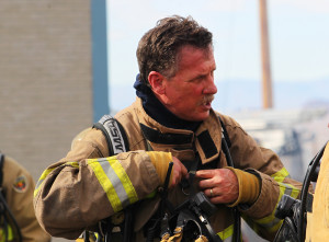 Dennis Mueller takes off his gear during his last live burn of his firefighting career. Jillian Danielson/RiverScene