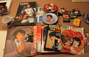 Evie displays some of her Elvis memorabilia she has colloected over the years including cassette tapes, magazines, mugs, and watches. Jillian Danielson/RiverScene