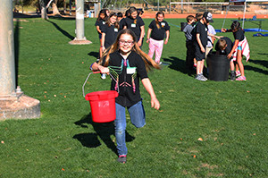 Taylor Ong carries a bucket full of water Wednesday morning during a water conservation lesson at Rotary Park. Jillian Danielson/RiverScene