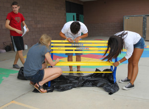 Madilynn Melodia, Michael Reinartz, and Jade Forman paint a buddy bench at Smoketree Elementary Friday morning. Jillian Danielson/RiverScene