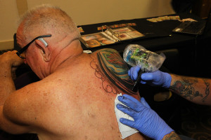 Dixie Smith gets tattooed by artist Larry Topping Saturday afternoon at The Tattoo Show. Jillian Danielson/RiverScene