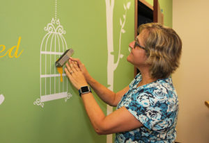 Kristine Kimball puts the finishing touches on a wall in the infants room Monday afternoon. Jillian Danielson/RiverScene