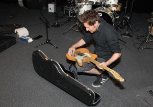 Jesse Pruett prepares the band instruments on stage Monday afternoon. Jillian Danielson/RiverScene