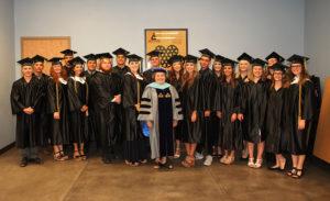 Dr. Sandy Breece poses for a photo with the Telesis Preparatory Acadamy graduates. Jillian Danielson/RiverScene