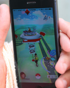 """A player battles for a """"gym"""" Friday evening on Pokemon Go. Rick Powell/RiverScene"""