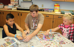 Eric assists students during an art project at Nautilis Elementary. Jillian Danielson/RiverScene