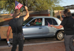 Eddie Dunn and Joan McDermott wave to an officer as he leaves the police department Monday evening. Jillian Danielson/RiverScene