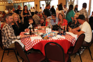 A group enjoys spaghetti at the Cooking With Cancer benefit. Jillian Danielson/RiverScene