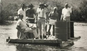 Robert McCulloch Sr. (white shirt), Robert McCulloch Jr. (shirtless), Ollie Heck (sitting in chair; McCulloch engineer), and others tour the river on a raft in 1959 looking over the layout of the land for the new Lake Havasu City. Photo Courtesy Musuem of History