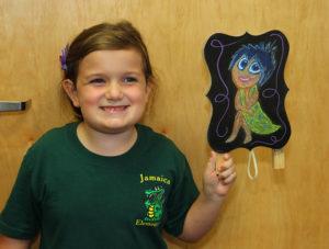 "Amelia holds a mini chalkboard drawing of ""Joy"" that Rosalyn drew for her to keep at home. Jillian Danielson/RiverScene"
