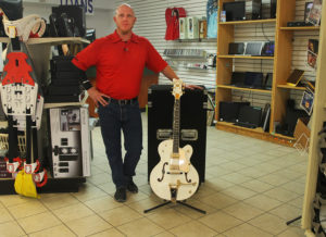 John Borders stand next to one of the items for sale in his shop, a Greutch Guitar. Jillian Danielson/RiverScene