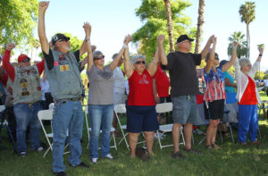 """People in attendance raise their hands during the playing of """"God Bless The USA"""" Sunday morning. Jillian Danielson/RiverScene"""