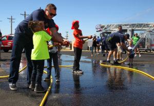Children learn how to spray a hose Saturday afternoon. Jillian Danielson/RiverScene