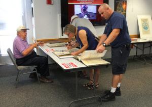 Freddy Grover, Cindy Irwin, and Mike Conelly look through old scrapbooks at the open house Saturday afternoon. Jillian Danielson/RiverScene