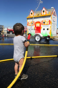 Valor Hunter learns how to spray a hose Saturday afternoon at the Fire Department open house. Jillian Danielson/RiverScene