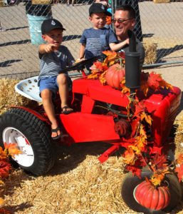 Cashton and Weston Falldorf and Joe Murdock play on a tractor at the Pumpkin Patch Saturday. Jillian Danielson/RiverScene