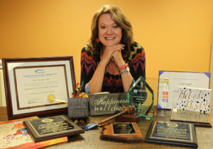 Lisa poses with things from around her office that makeup up some of who she is including awards, her love for chocolate, and even a Transformer that her grandkids play with. Jillian Danielson/RiverScene