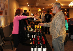 """Christy """"Critter"""" Thomas pours Fred Hahn a glass of wine at Havasu Top Chef Thursday evening. Jillian Danielson/RiverScene"""