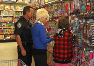 Officer Erhart, Dee Erhart, and Michaela Beach shop for Barbies Saturday morning during Shop With A Cop. Jillian Danielson/RiverScene